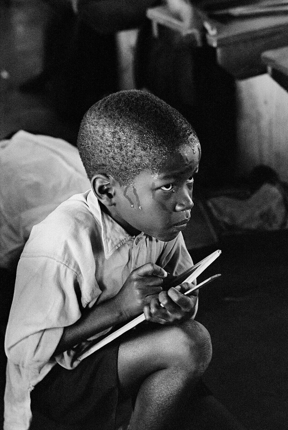 Ernest Cole, Earnest boy squats on haunches to follow lesson in heat of packed classroom, Gauteng [Transvaal], South Africa, c.1965 (from The House of Bondage)